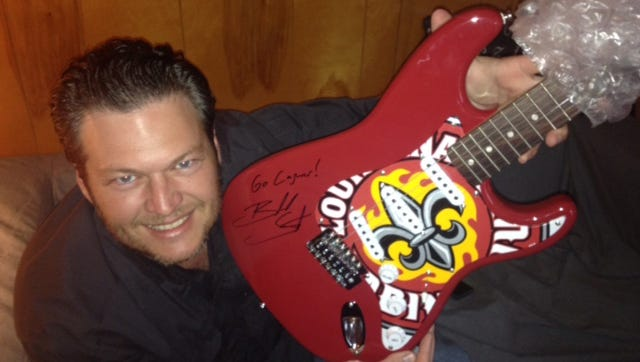 Country music singer Blake Shelton displays the guitar signed by the singer and featuring a Ragin' Cajun motif that will be auctioned during the UL Alumni Association's 2015 Spring Gala