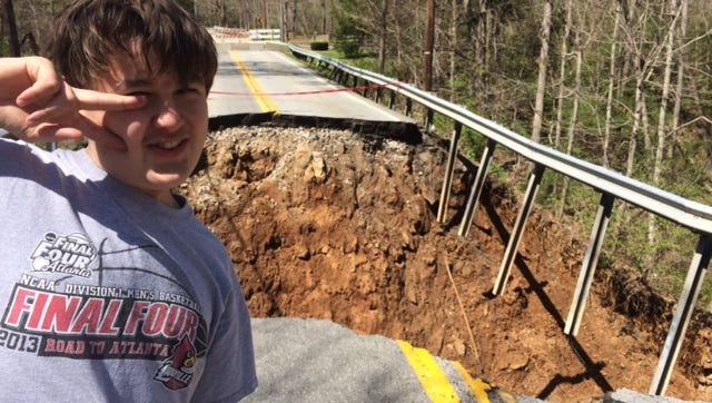 Gregory Watkins, 12, who attends Barret Middle, checks out the collapse of Brownsboro Road near Spring Valley.