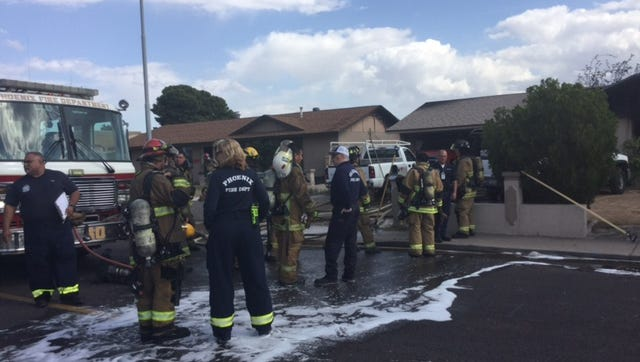Phoenix firefighters at the scene of a fire that spread from one home to another on Friday, April 24, 2015.