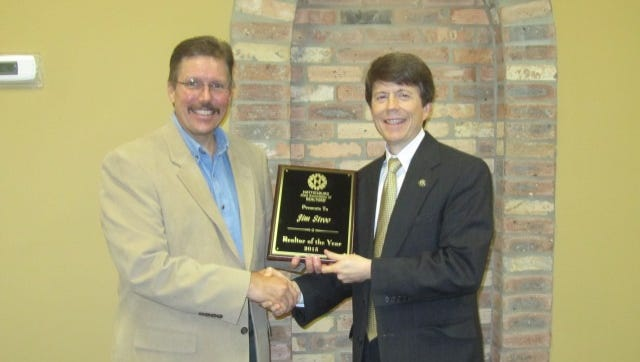 Paul Dunbar, broker/owner of Dunbar Real Estate, presents Jim Stroo with the 2015 Realtor of the Year Award.