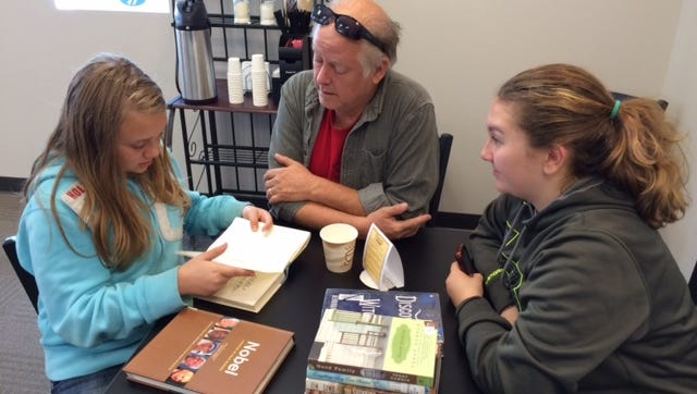 Scott Kinter, center, of Waterloo, Iowa, was camping with his granddaughters Ashlyn Kjer, left and Grace Kjer of Kewaskum, and brought them to the grand opening of Chapter 52 on Sept. 12 in downtown Fond du Lac. The used bookstore is operated by the Fond du Lac Public Library.