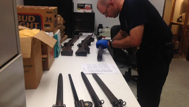 Lab Specialist Andrew Olson checks serial numbers Friday afternoon on stolen gun recovered by the Battle Creek Police Department.
