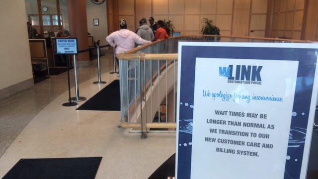 Sign warns of customer service delays at Louisville Water headquarters.