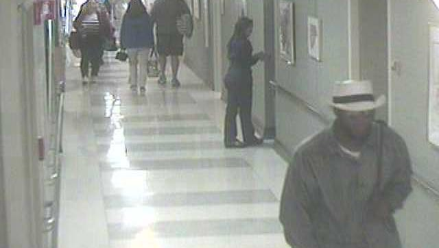 Video surveillance of   suspect, front right, in armed robbery of parking garage employee at Morristown Medical Center