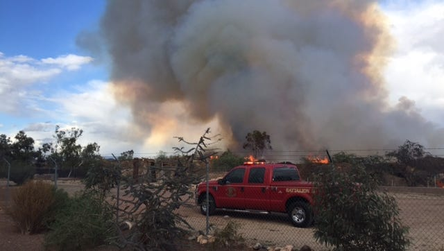 About 80 firefighters were working to prevent a mulch fire burning near Jomax Road from moving toward Interstate 17 in north Phoenix on Nov. 4, 2015.