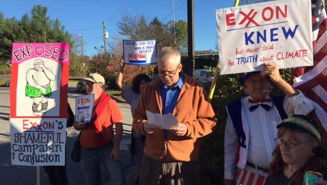 Greg Yost, left, reads a statement during a protest on global warming at an Asheville Exxon station Tuesday.