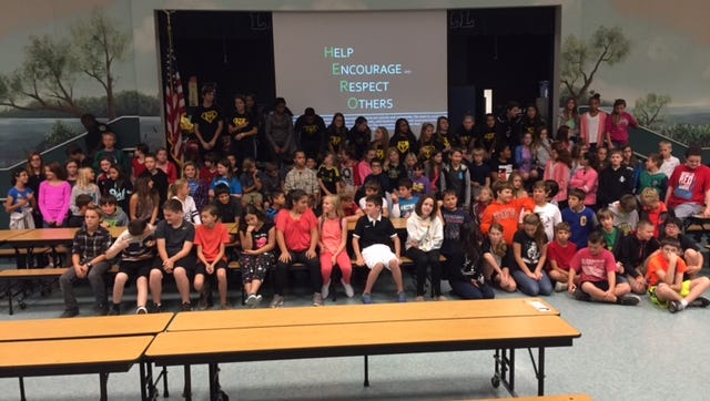 Students from Merritt Island High School and Lewis Carroll Elementary pose for a picture.