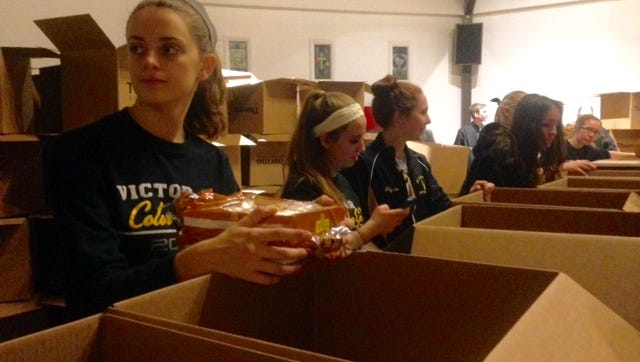 Erin Whipple, of Victor, left, packs bread into boxes for Saturday's Give Around Victor Day event on Dec. 18, 2015.