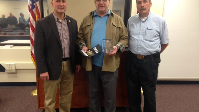 Sheriff John Fuson presented a plaque to Sgt. Larry McCrobie at a retirement party Friday.