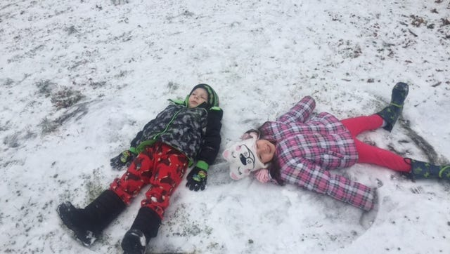 Shawn and Alayna Dwyer attempt to make snow angels in their Mt. Juliet yard on Wednesday.