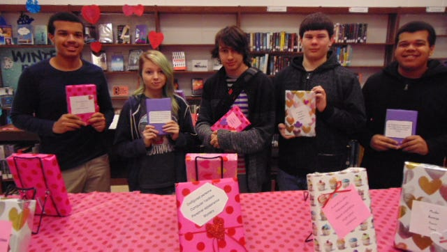 "(From left) Ethan Bryan, Kayla Mooney, Daytona Spradling, Tanner Cossaboon and Jalen Bryan, students at Millville Senior High School, show off their ""Blind Date with a Book"" selections."