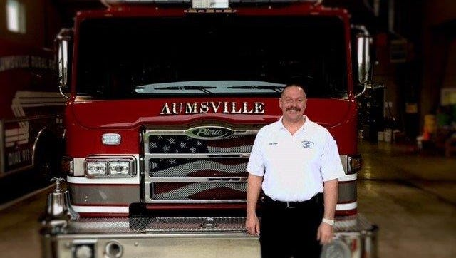 Fire Chief Terrill Isaak stands with one of Aumsville Rural Fire District's new fire trucks.