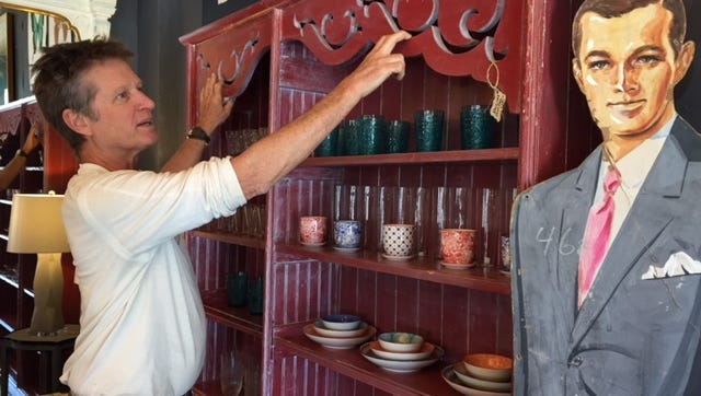 Greg Taylor, owner of Change Everything, shows off shelving he created from various woods and architectural pieces.