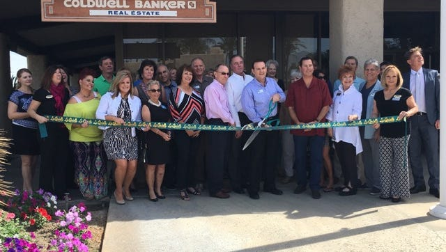 Mark Bennett, manager of Coldwell Banker Residential brokerage's new Indian Wells-La Quinta office,  cuts a giant ceremonial ribbon in celebration of grand opening.