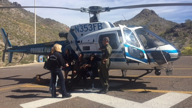 Phoenix rescue personnel sit around the Firebid 10 helicopter, which is used to rescue distressed hikers.