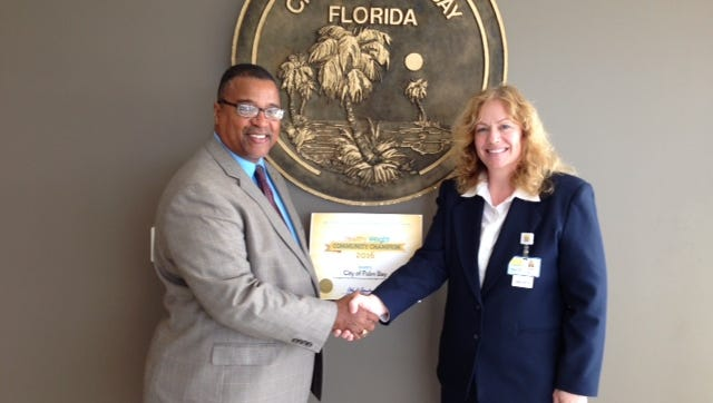 Palm Bay Mayor William Capote accepts an award from Sophia Tomadakis of the Brevard County Health Department, recognizing the city as a community champion in the  Healthiest Weight Florida contest.