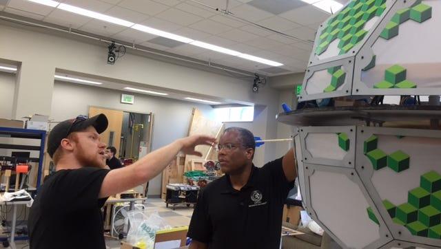 Mechanical Engineering graduate student Tyler Jonas showing CISCOR Director Emmanuel Collins a Mechatronics in Art class project