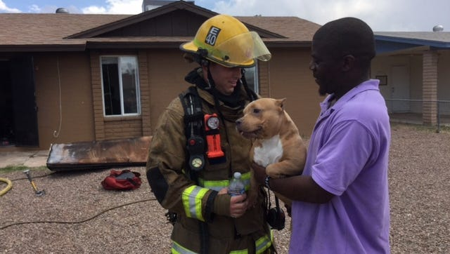 A Phoenix firefighter with a dog rescued from a house fire near 90th Drive and Roma Avenue Saturday afternoon.