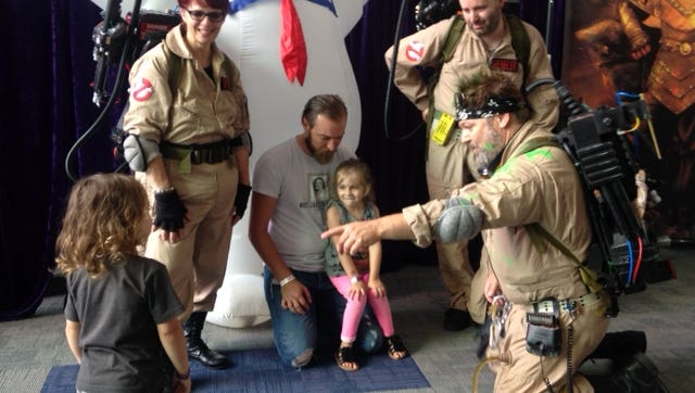Connor Green of Buffalo, center, introduces two of his children to the Ghostbusters crew at the Strong National Museum of Play Saturday.