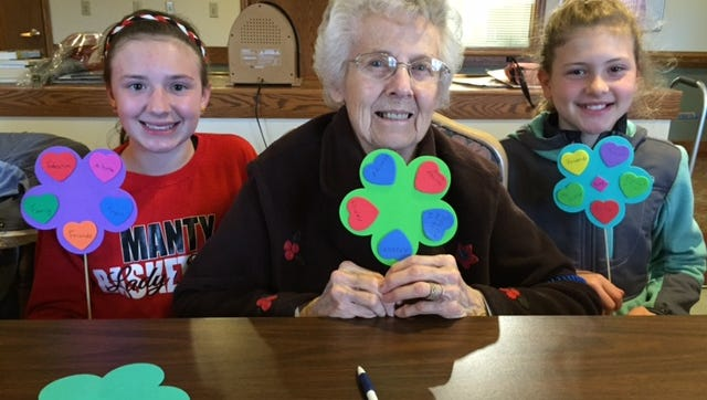 Ellie, student (from left), Eleanor, Felician Village resident, and Karenna, student, enjoyed an arts and crafts project together.