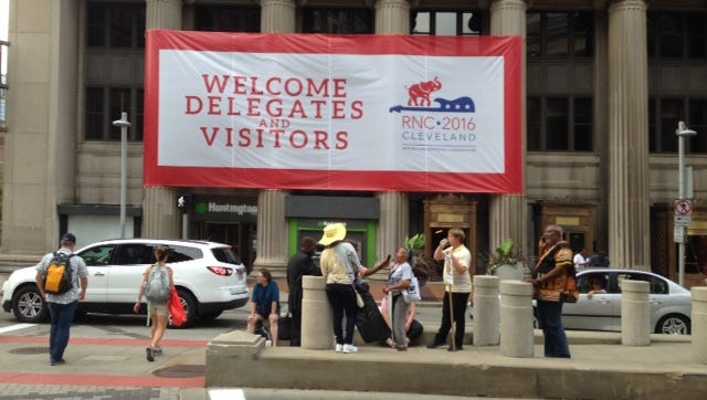 Black Lives Matter protesters under and GOP welcome banner in Cleveland.