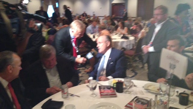 Former New York Mayor Rudy Giuliani speaks to a reporter in Cleveland.