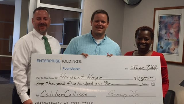 Tyson Bragg and Aritha Richardson of Enterprise Rent-a-Car present Graham Whitlock (middle) of Caliber Collision with a $1500 check towards the company's 5th annual Rhythm Restoration Food Drive to benefit Harvest Hope Food Bank.