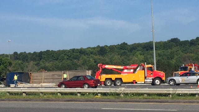 No one was injured when a southbound semi flatbed tractor trailer on Interstate 71 tipped over Monday morning, snarling traffic as the load of prefab concrete walls spilled onto the highway.