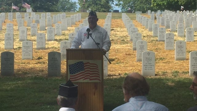 Tony Delong, director of the Richland County Veterans Service Commission, addresses the crowd at Mansfield Cemetery on Tuesday during the re-dedication of the markers, which were aligned in the Veterans Honor Ground.