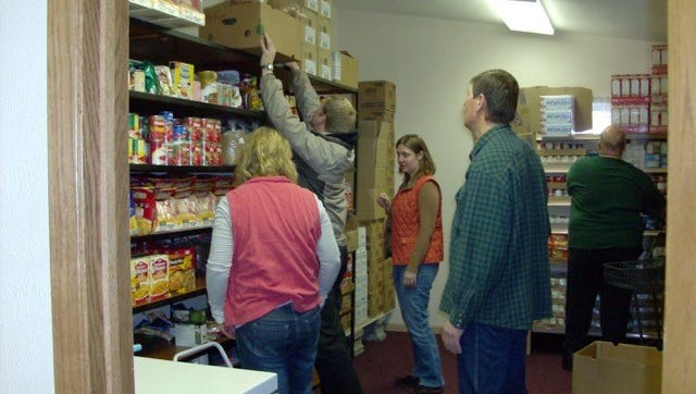 Volunteers stock the shelves of the Community Alliance Food Pantry, which serves the Owen-Withee area.