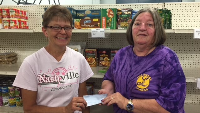 Lynn Skarvan, of the Two Rivers/Mishicot Ecumenical Food Pantry, receives a $500 check from Two Rivers Lioness Club president Sandi Moore to be used toward the replacement of the food pantry's truck.