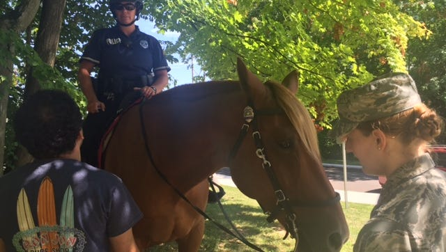 OSU student Tim Gesouras, at left, talks with OSU police Officer Regina Shoopman and her horse Red as Airman First Class Gwendalyn Smith looks on at the OSUM/NCSC Involvement and Community Fair on Thursday.