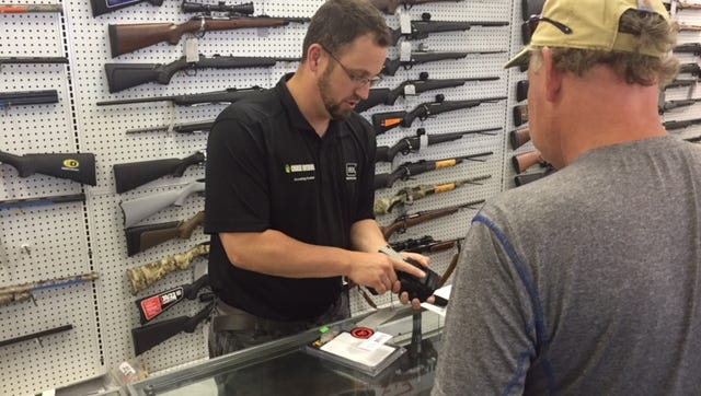 Chase Outdoors owner Justin Gaiche educates a customer on how to properly use a gun holster.