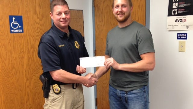 Earl Seliskar of Investors Community Bank presents a check to the Plover Police Department for their K-9 program.