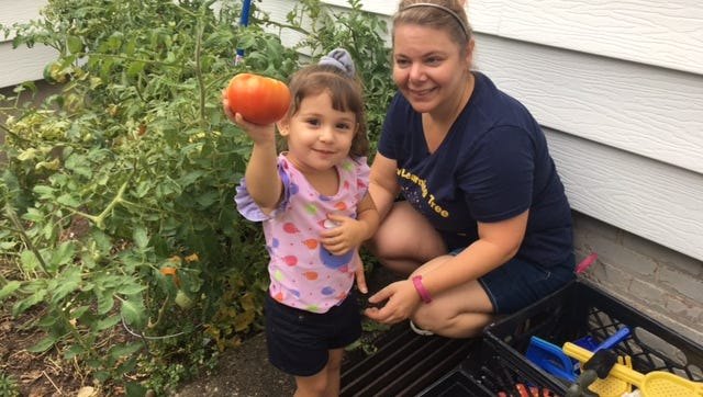 Earth-friendly lessons start early at Learning Tree Preschool in Hawthorne, the winner of the Green Business Recognition Award for 2016. Here Mia Fiscella, accompanied by Diane Oliver, shows off a  tomato she helped to grow in the school's garden.