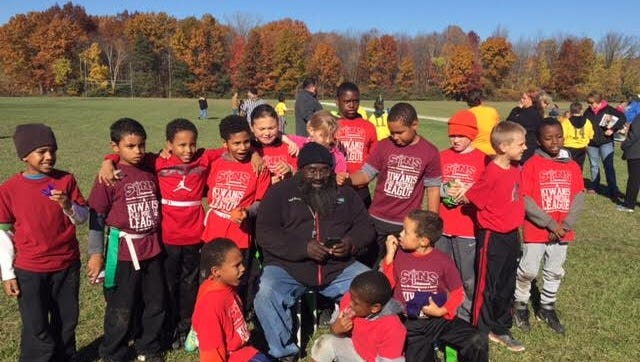 Buddy Sutherland is surrounded by some of the athletes of the Kiwanis Flag Football League.