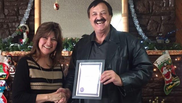 Angie Olivas awards Gary Lynch the National Association of REALTORS Emeritus Dec. 19.