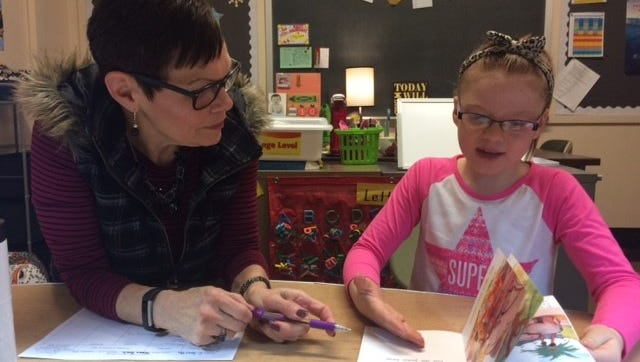 Cindy Smith, a reading specialist, helps Waters Elementary School first-grader Tessa Zoch with a Reading Recovery program. The goal is to boost student literacy at a young age.