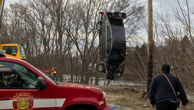 A car pulled from the Kalamazoo River on Sunday evening hangs from a crane's cable on the south bank.