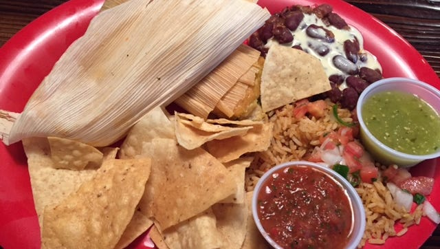 SoKno Taco Cantina serves a fried cornmeal-wrapped tamale platter that comes with fiesta rice and cast-iron beans — kidney beans infused with house seasoning and topped with queso.