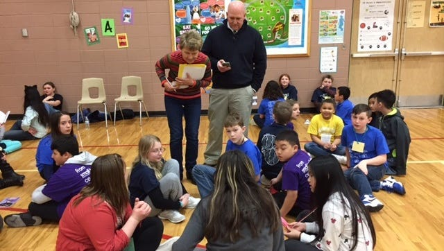 Retired SASD administrator Marty Steinbruecker and Grant principal Jim Renzelmann read questions to a group of students at the Battle of the Books.