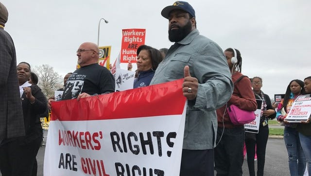 Billy Dycus, president of the Tennessee AFL-CIO Labor Council, far left, holds a sign with Mike D. Payne of Fort Lauderdale, Fla., and Evelina Warlix of Memphis at a rally.