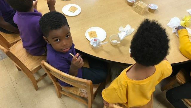 Preschoolers at Perea Preschool enjoy an afternoon snack while waiting for their parents - many of who are learning how to use dance, theater and therapy to rear their children healthy emotionally.