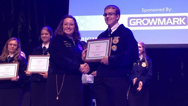 Wisconsin FFA President Brenna Bays presents Casey Kroening of Ladysmith, the award for being named the Wisconsin state winner of the 2017 GROWMARK essay contest for FFA members.