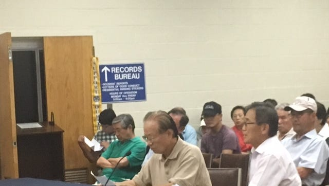 Hyukman Kwon of Palisades Park brings an interpreter, James Chung, to a Palisades Park council meeting held August 8.