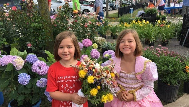 Sisters Abigail and Elizabeth Perrot of Farmington were excited to pick out fresh flowers for mom at the farmers market.