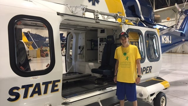 Ben Lepisto poses next to a state chopper on his way to Disney World. The Mercer County Sunshine Foundation uses donations to take young patients to Disney World every year.