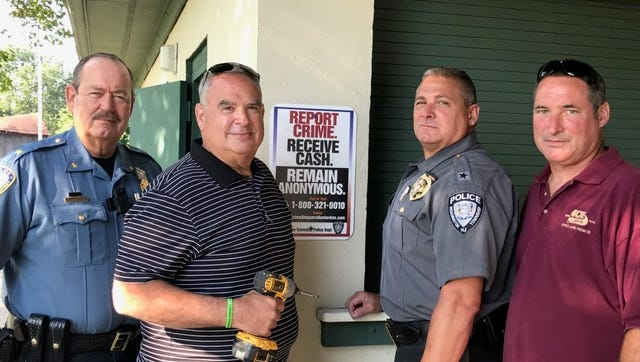 Anonymous tips that fight crime in our communities. Frenchtown Police Chief Allan Kurylka, Crime Stoppers board member Vince Nardone, Readington Police Chief Sebastian Donaruma and Readington DPW representative Wade Warner install a sign at Hillcrest Park in Readington.