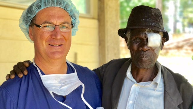 Dr. Michel Gelinas poses with a patient they helped ragain his sight.