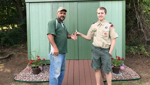 Boy Scout Christopher Handel hands John Ostering the keys to the shed he completed for his Eagle Scout project.